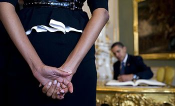 First Lady Michelle Obama waits as President B...