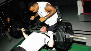 A Man (lying Down) Performs A Bench Press With A Spotter Using A  Potentially Dangerous Thumbless Grip.