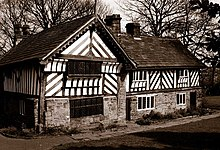 Photograph showing a timber-framed house. There are tow sections to the building at right angles to each other forming a T shape. The ground level of the building has stone walls, whereas the upper floor has wattle and daub infill.