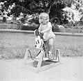 Blond kindje op Mickey Mouse hobbelpaard in Suriname, Bestanddeelnr 252-6872.jpg