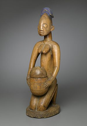 Ajere Ifa - This kneeling figure was probably carved by Maku, the master carver of the town of Erin, or by Toibo, his son. The elongated oval head, set on a slightly curved neck, the stylized ears, and the incised lines across and below the half-closed eyes are characteristic of these carvers. The figure probably served as a receptacle for small gifts on a shrine altar, possibly dedicated to Shango, the god of thunder and lightning.