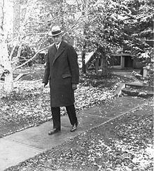 A man in a hat and overcoat walks down the front walk of a house. There is snow on the ground.