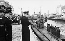 Several people looking at a submarine with its crew on the deck