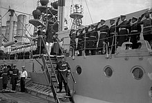 Men in military uniforms walk down stairs on a large warship as dozens of sailors look on and salute.