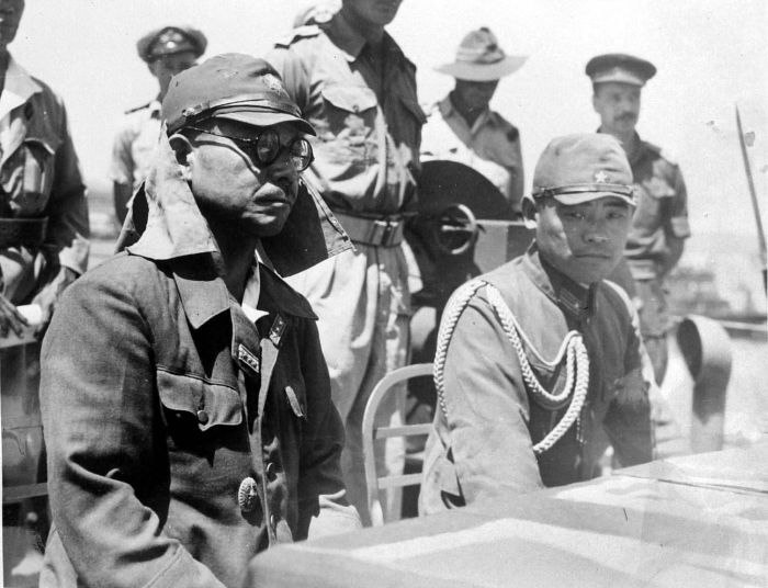 Kaida Tatsuichi, commander of the Japanese 4th Tank Regiment, and his chief of staff Shoji Minoru listen to the terms of surrender on HMAS Moresby at Timor.