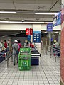 Cashier of an Tesco supermarket in China, with counters marking international credit cards accepted.jpg