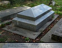 Een granieten, horizontale, geometrisch uitgewerkte grafsteen omringd door andere grafstenen