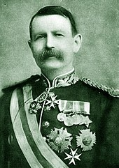 Moustached man in uniform emblazoned with medals