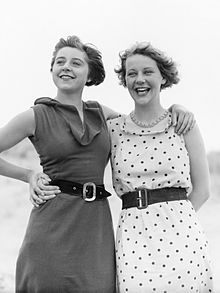 two young women in sleeveless dresses hugging