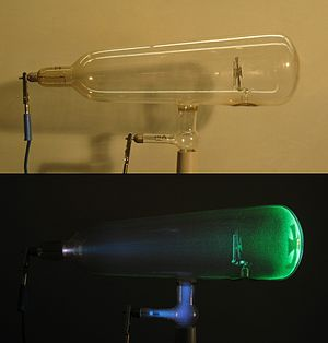 Crookes tube - A Crookes tube: light and dark.  Electrons (cathode rays) travel in straight lines from the cathode (left), as shown by the shadow cast by the metal Maltese cross on the fluorescence of the righthand glass wall of the tube.  The anode is the electrode at the bottom.
