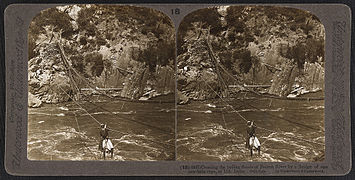 Crossing the boiling floods of Jhelum River by a bridge of one raw-hide rope, at Uri in Jammu and Kashmir (c. 1903).jpg