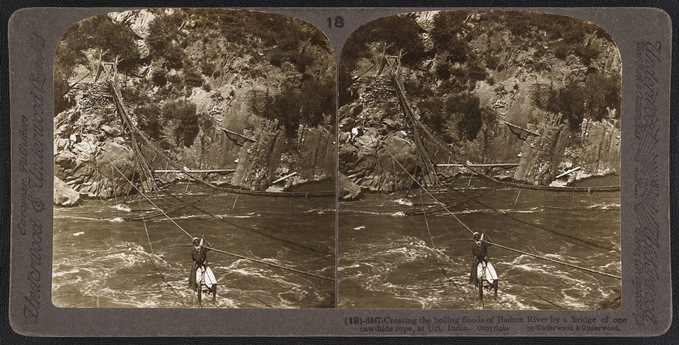 Crossing the boiling floods of Jhelum River by a bridge of one raw-hide rope, at Uri in Jammu and Kashmir (c. 1903)