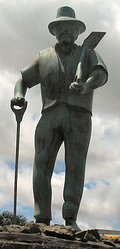 Stone statue of a middle aged-man with a beard, a shovel, and some other similar instrument
