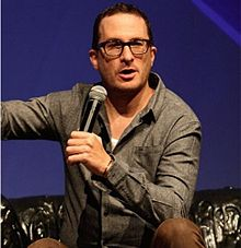 Aronofsky kneeling while holding a microphone