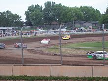 Cars race around a dirt course behind a tall metal fence.