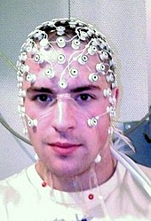 Photograph of a subject's head with numerous small sensors covering the forehead, neck and scalp