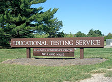 "Large wooden sign with ""Educational Testing Service"" in white letters, on the law in front of ETS headquarters."