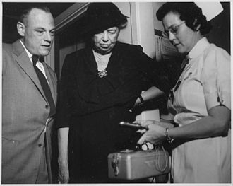 Oak Ridge Associated Universities - Eleanor Roosevelt (center) and Dr. William Pollard watch as Nurse Mary Sutliff demonstrates a radiation counter during Roosevelt's 1955 visit to the Oak Ridge cancer research hospital. (Photo by Ed Westcott)