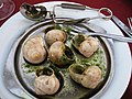 Escargot on a plate with special tongs and forks to use for eating.