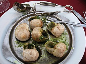 Plate of escargot with tongs and fork, taken i...
