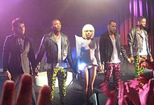 A group of five people (four men, one woman in the middle) standing. The men are dressed in black jackets and colorful pants. The lady looks towards the camera and is wearing a short blue dress. She is holding a stick in her right hand. The head of the stick is illuminated by a glowing bulb