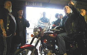 59 Club - Father Graham Hullet, a leader of the 59 Club seated on motorcycle, with original 59 Club members at the Enfield Motorcycles factory, UK