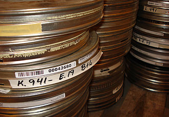 Film preservation - Stacked film cans containing rolls of film.
