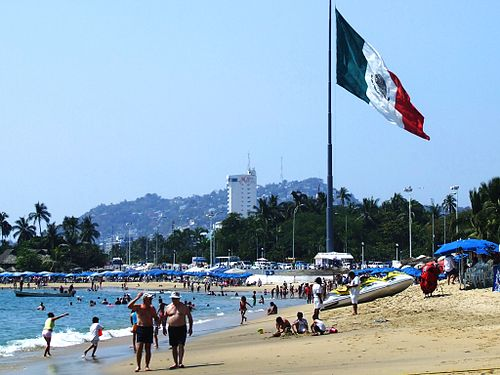 A view of Acapulco's beach with a Bandera monumental in the background Flag of Mexico in Acapulco.jpg