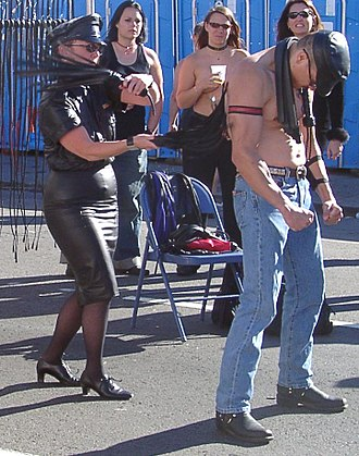 Impact play - In this flogging demonstration at Folsom Street Fair 2004 the top is using an advanced double flogger technique.