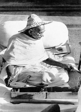 Madhur Jaffrey - Mahatma Gandhi wearing a Noakhali hat while spinning khadi at Birla House, November 1947.