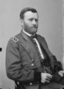 Bearded man in an army uniform, sitting