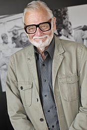 an older man with black glasses smiles at the camera.
