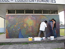 Photograph of George Simon and Anil Roberts at work on the Palace of the Peacock mural at the University of Guyana (2009)