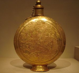 Economic history of China before 1912 - A Chinese dragon seen floating among clouds, engraved on a Ming-era golden canteen (15th century).