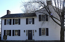 A two-story structure with white siding and windows with black shutters