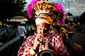 Guadeloupe winter carnival, Pointe-à-Pitre parade. A trumpet-player wearing traditional carnival head-dress and outfit(close up outdoor portrait).jpg