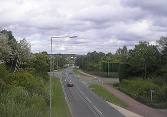 Milton Keynes grid road system - A typical single carriageway grid road, H4 Dansteed Way, looking east from Two Mile Ash. Note the tree lining, the redway cyclepath and the staggered junction for local roads.