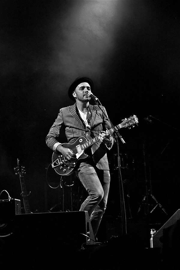 A black and white photo of musician Hawksley Workman standing on stage, playing guitar in front of a microphone with a beam of light on him.