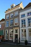 foto van Huis met dwars zadeldak tussen tijtopgevels; kroonlijst met gesneden consoles; ingangsomlijsting met gesneden kalf