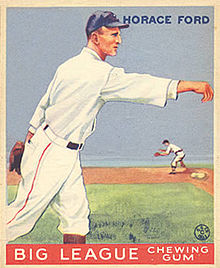 A baseball card image of a man with a strong nose in a white old-style baseball uniform and blue baseball cap