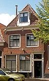 Huis met laat 18e-eeuwse gevel met rechte kroonlijst waar rocococonsoles; omlijste deur, voor wellicht ouder pand