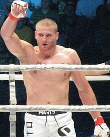 Jan Błachowicz in the ring celebrating vitory with his right hand in the air.