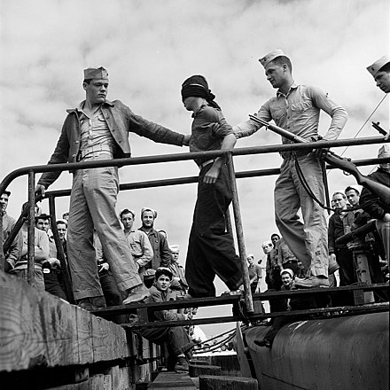 A Japanese POW being led off a US Navy submarine in May 1945. Japanese POW being led off a submarine.jpg