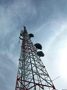 A photograph at a close, upward angle of a radio tower.