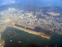 Aerial view of a runway of an airport. It is surrounded by a harbour.