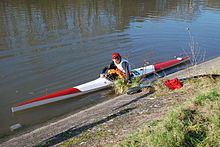 Long, thin kayak with blunt bow and stern, on flat water, person getting in