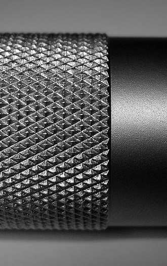 Knurling - Close-up shot of a diamond-pattern knurling on a cylindrical work piece. Knurling method: left/right with tips raised, spiral angle: 30°, pitch: 1 mm, profile angle: 90°