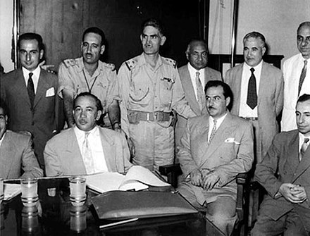 Leaders of the 14 July 1958 revolution in Iraq, including Khaled al-Naqshabendi (front row, left), Abd as-Salam Arif (back row, second from left), Abd al-Karim Qasim (back row, third from left) and Muhammad Najib ar-Ruba'i (back row, fifth from left). Also included is Michel Aflaq (front row, first from right). Leaders of July 14 1958 Revolution.jpg