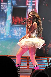 A brunette teenager from a left profile singing into a microphone. She is wearing a short, white tutu dress.