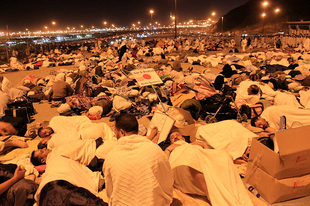 Groups of pilgrims in white cloth sitting on rocky ground under a light in the middle of the night.